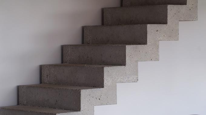 Gros plan d'une partie droite d'un escalier qui a été poncé et laisse brut