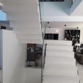 audacieux  escalier crémaillère avec palier intermédiaire en béton ciré vernis soyeux couleur everest Blanc pur, à Saint remy l honnore en région parisienne.  pour un constructeur