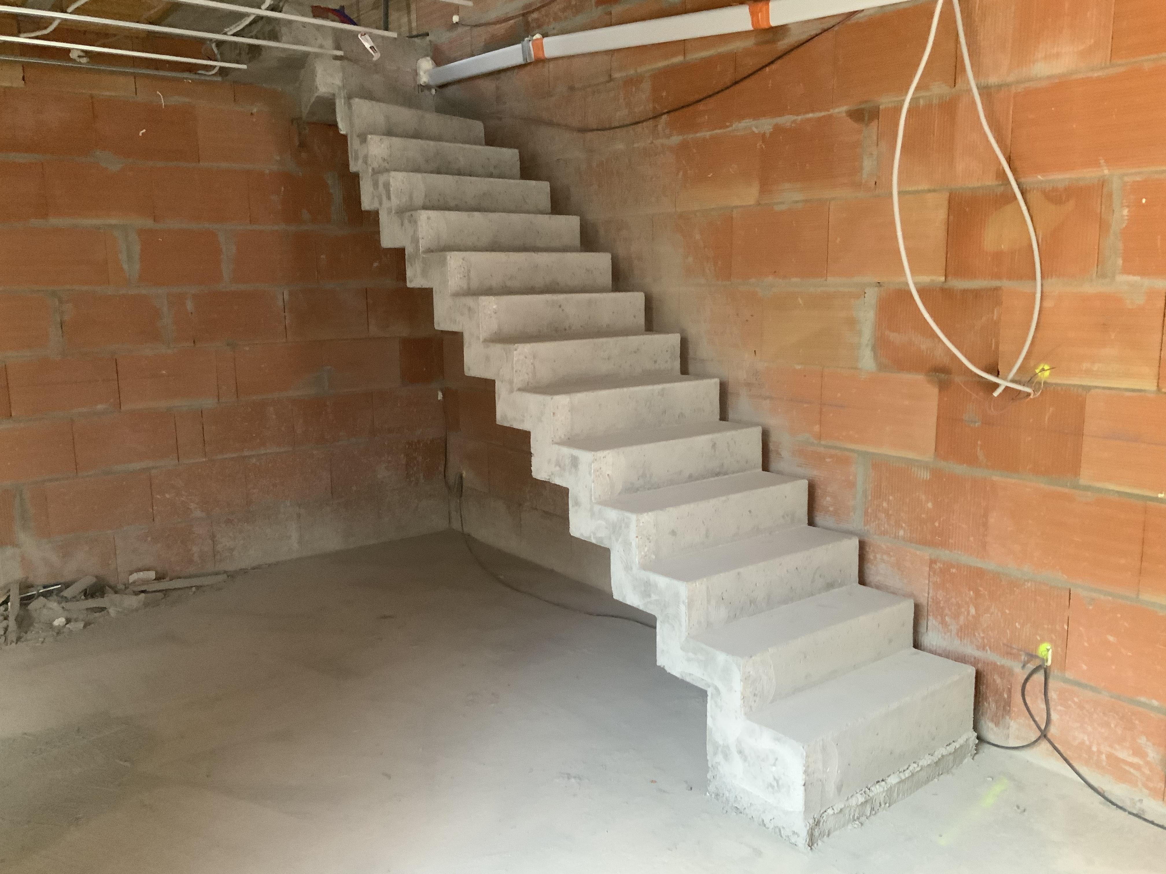 Départ de l'escalier avec sa première marche haute où à été pris en compte la réservation pour le futur plancher chauffant du rez de chaussé de la maison