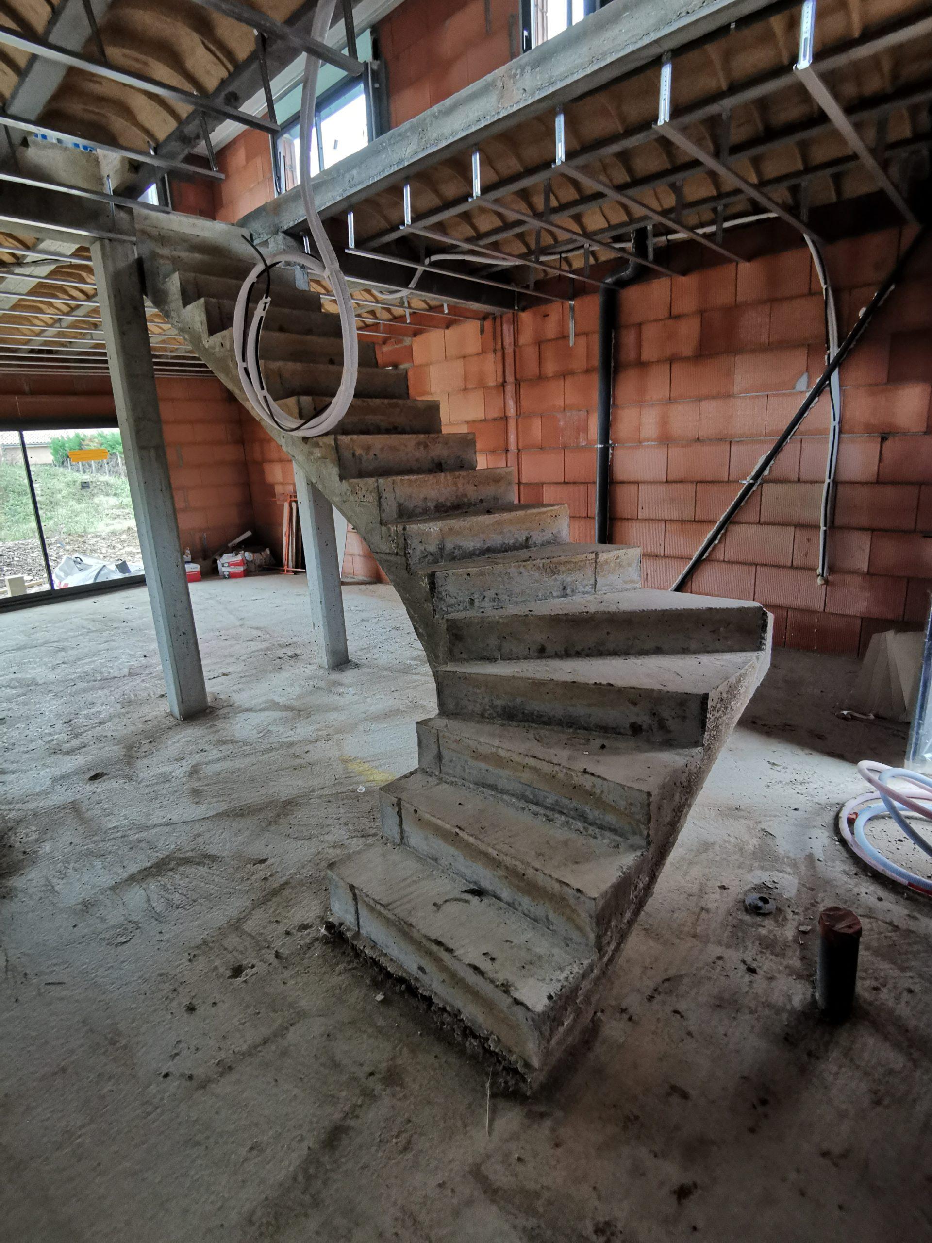 Départ de l'escalier en quart tournant à gauche pour accéder à l'étage de cette maison individuelle en construction