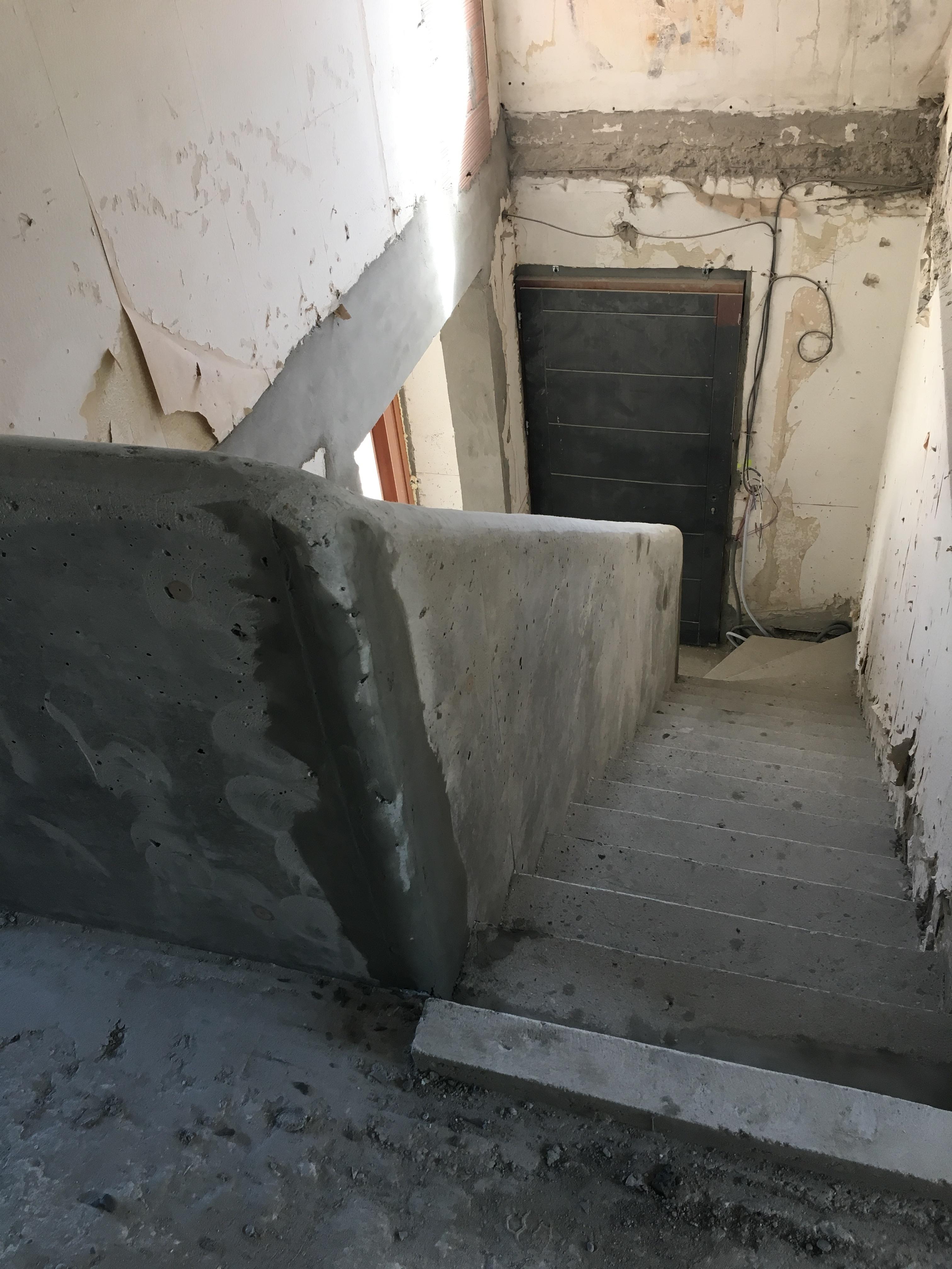 Descente de l'escalier béton et de son garde corps dans une maison en rénovation