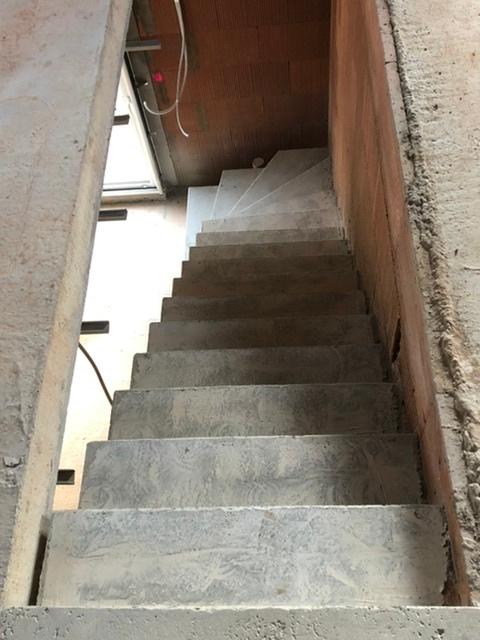Escalier beton brut de décoffrage le long d'un mur en brique.
