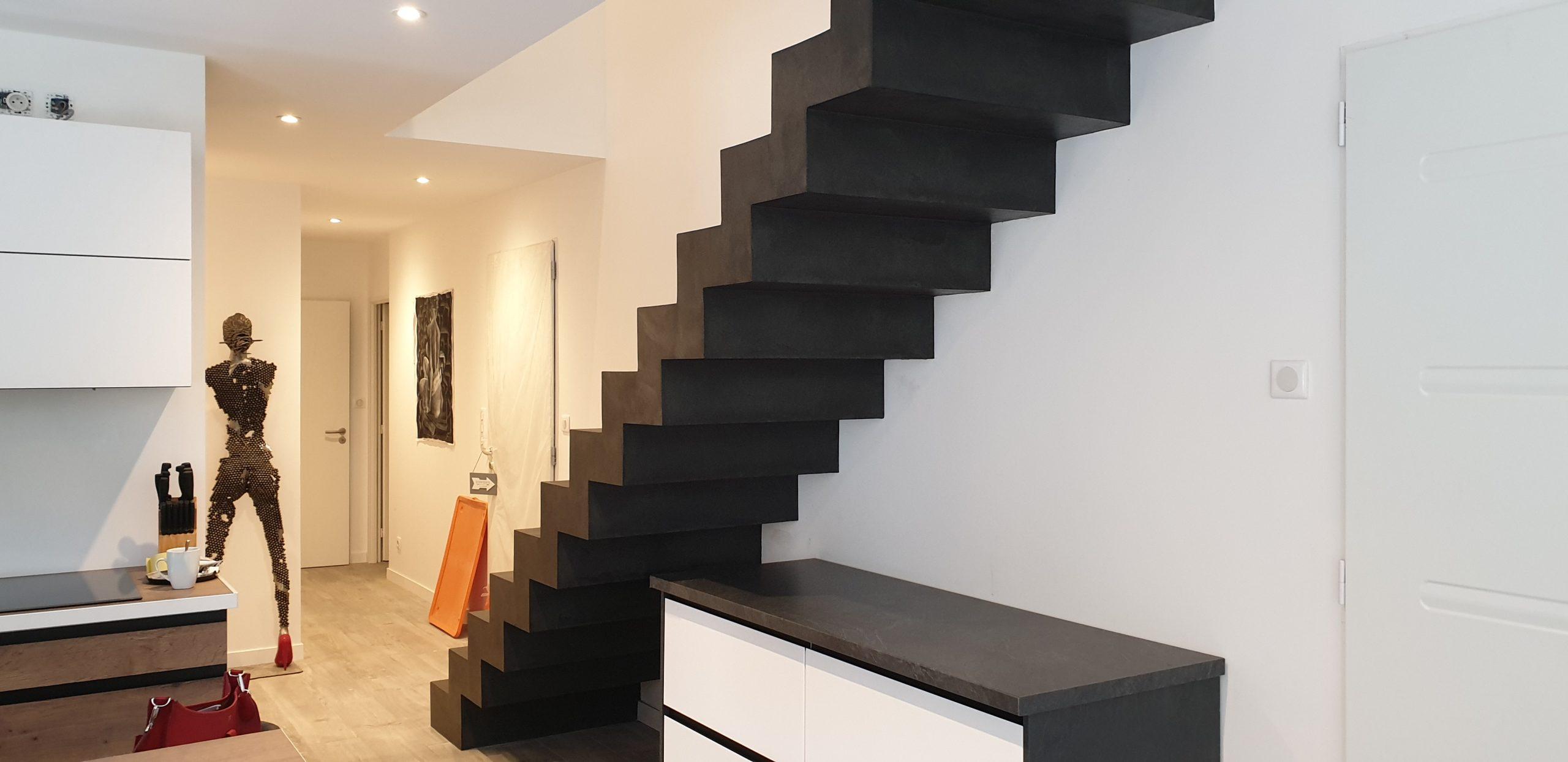 Escalier béton décoré en béton ciré couleur ardoise pour trancher avec le mur blanc du fond
