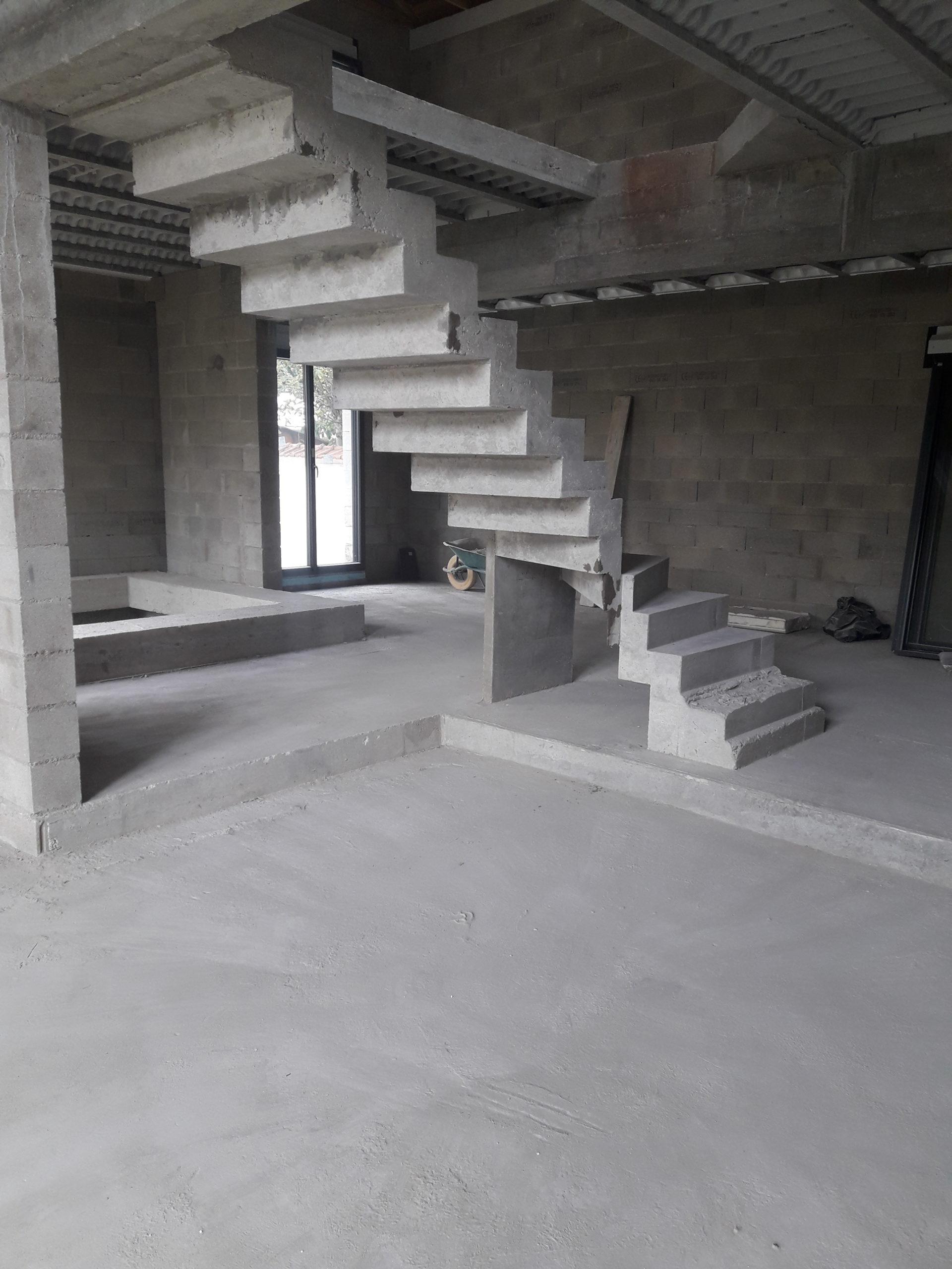 Escalier béton design tournant dans une maison en construction