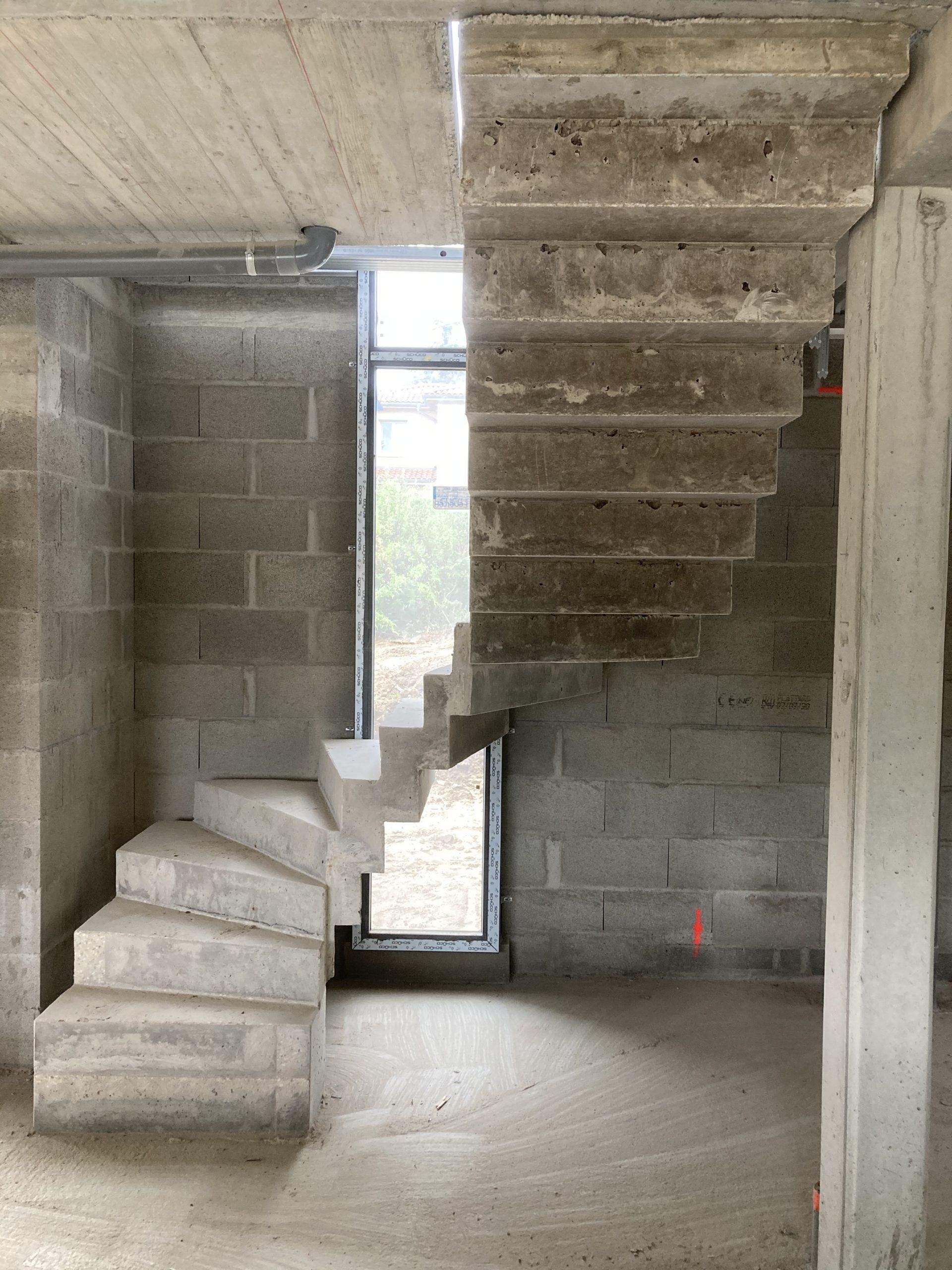 Escalier béton devant une baie vitrée dans une maison individuelle
