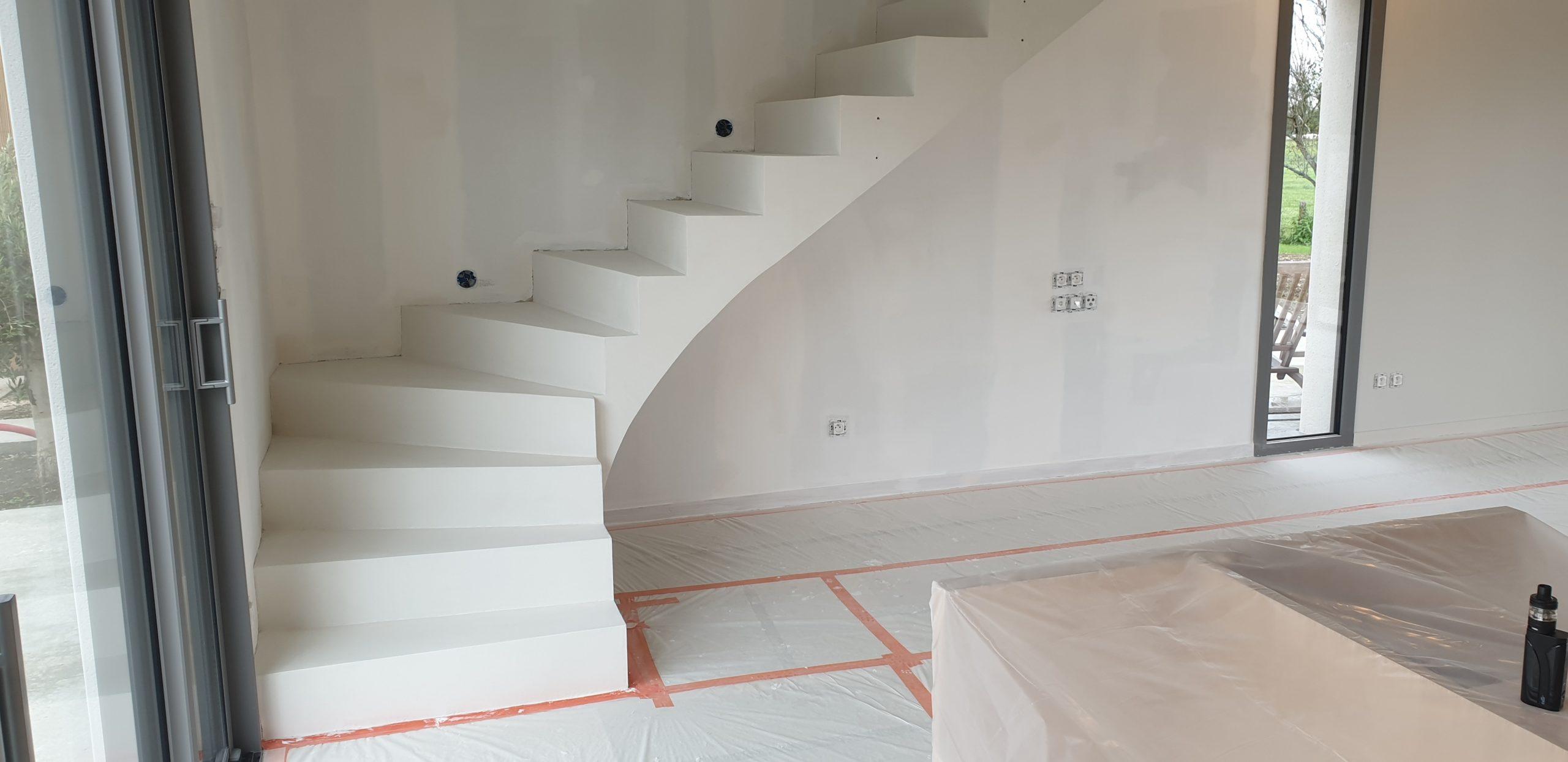 Escalier coulé en béton brut puis revêtement en béton ciré blanc dans une maison en construction