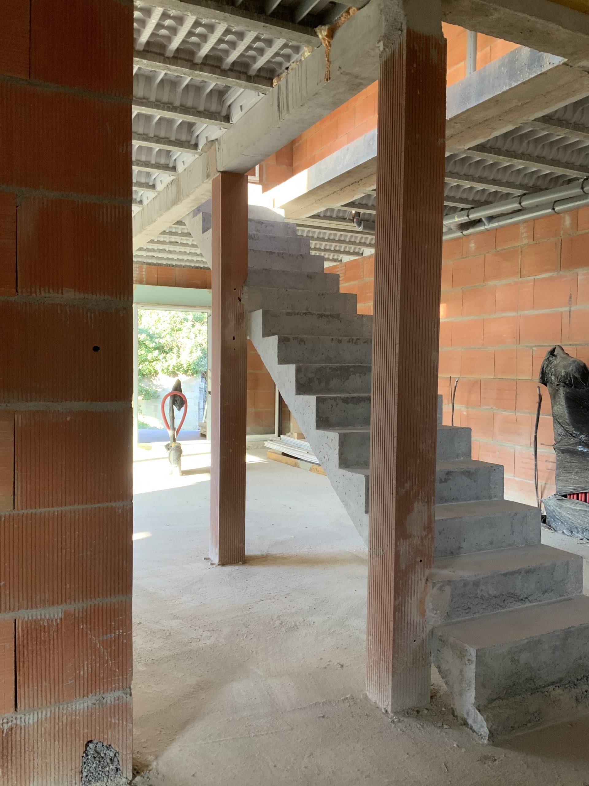 Escalier droit entre deux poteaux dans une villa en briques en cours de construction