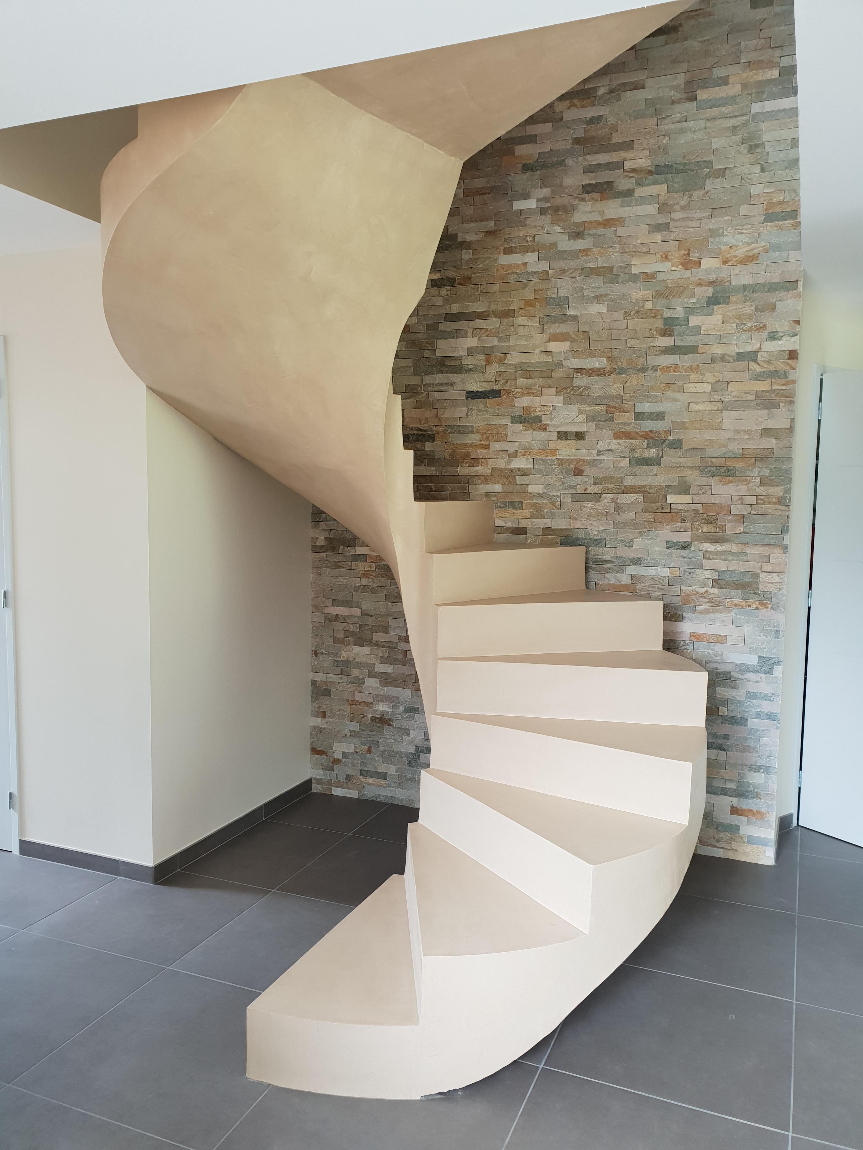 Escalier hélicoïdal en béton ciré sur un fond de mur en pierre