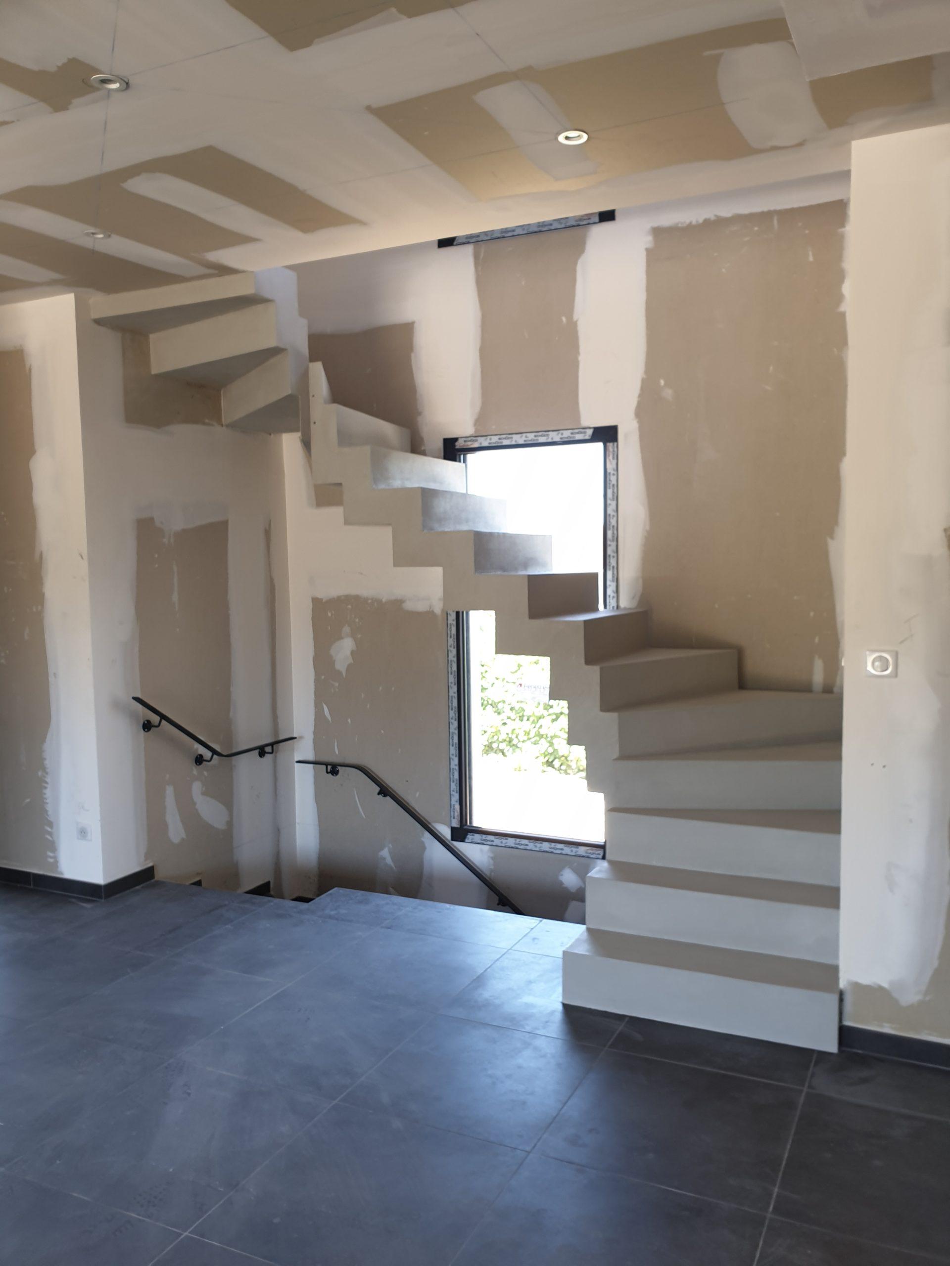 L'escalier béton traverse une baie vitrée en plein milieu