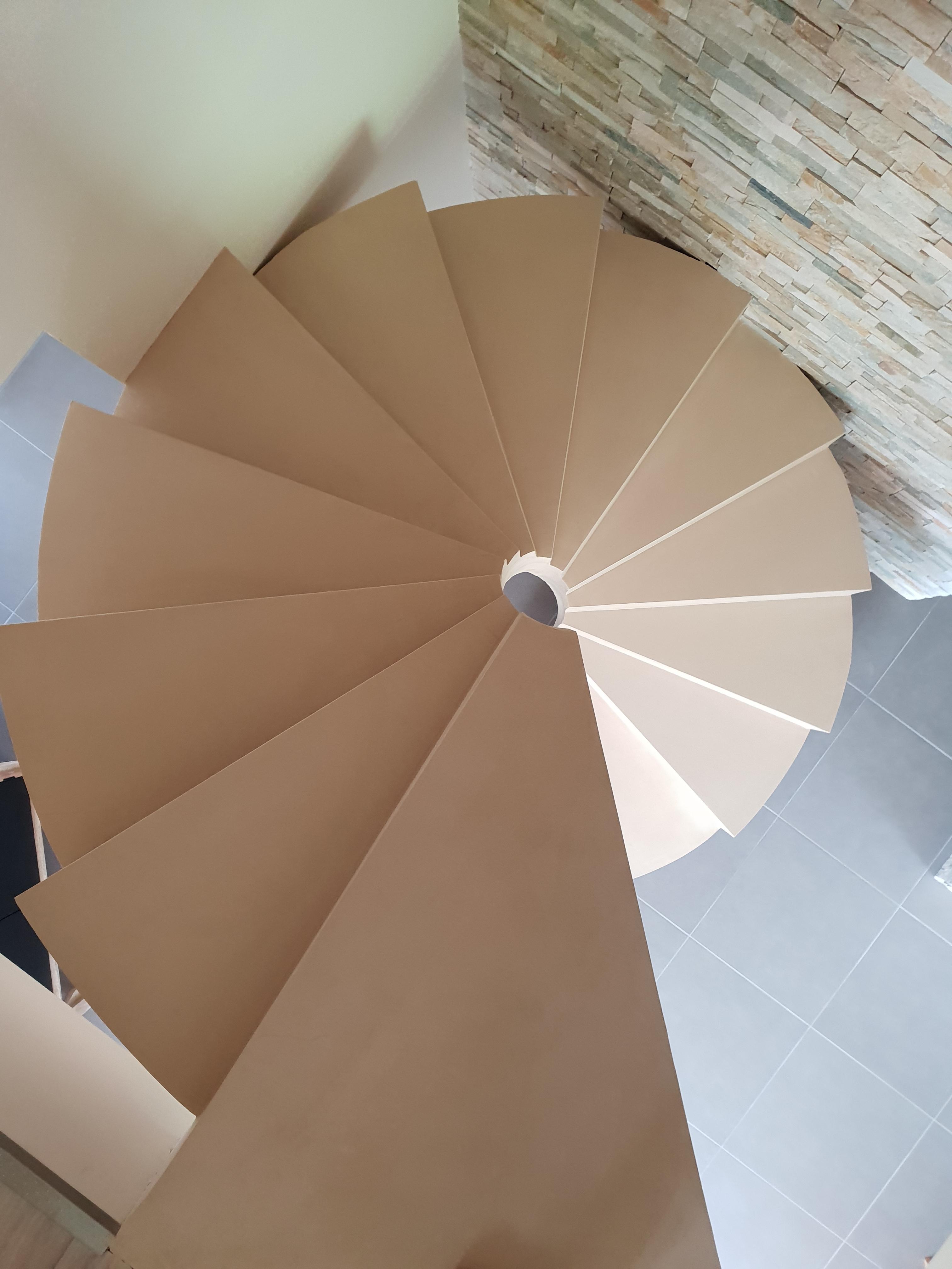 Marchés en béton ciré et lumière centrale d'un escalier hélicoïdal