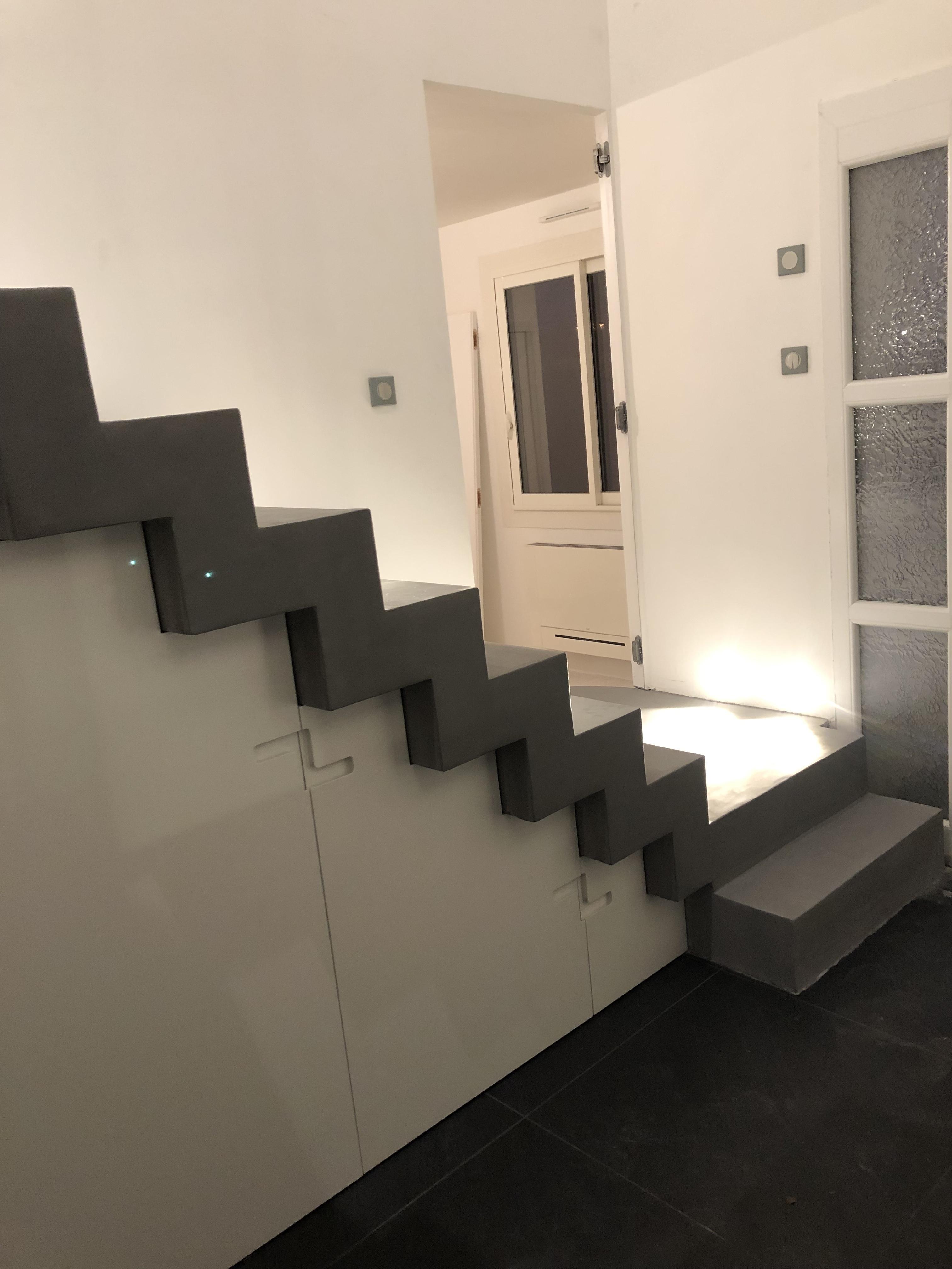 Placard sur mesure sous un escalier béton ciré gris foncé